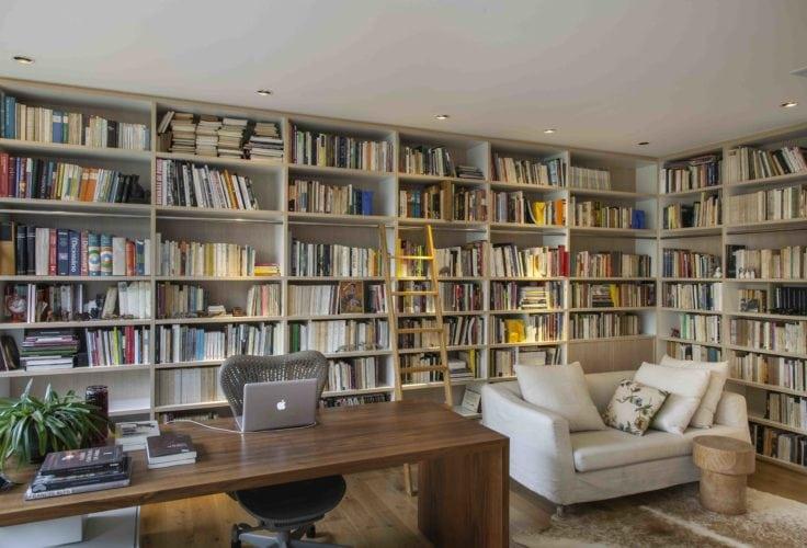 Estante de livros escrivaninha e sofá branco no apto assinado por Tania Eustáquio