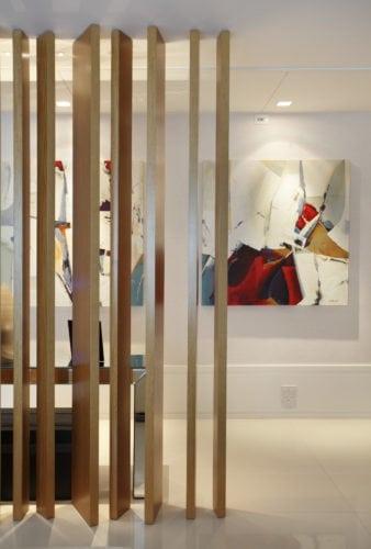 ÁREAS INTEGRADAS E COM MARCENARIA VALORIZADA. Ripas em madeira, separam o hall de entrada da sala.