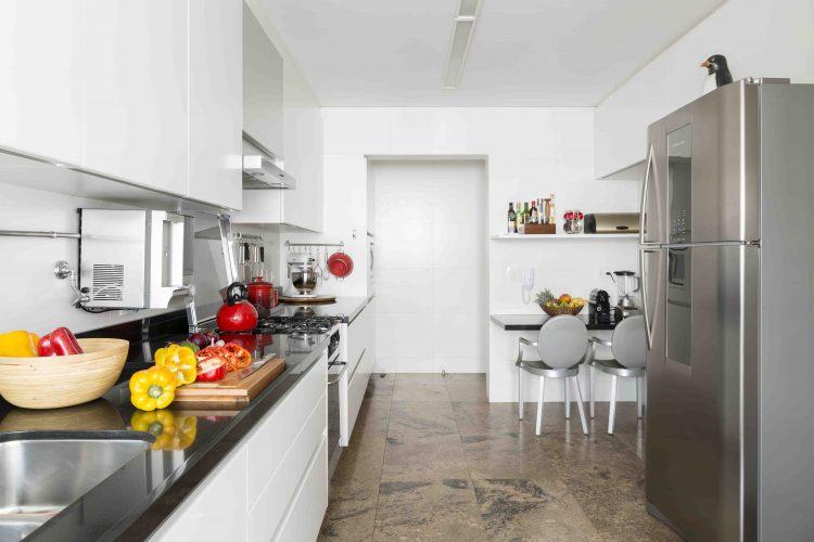Cozinha branca com cadeiras de Phillipe Starck no apartamento assinado por Denise Barretto