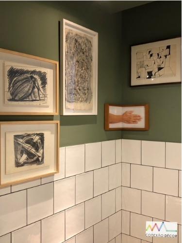 Cozinha com meia parede em azulejo branco, parede pintada de verde e quadros na parede.