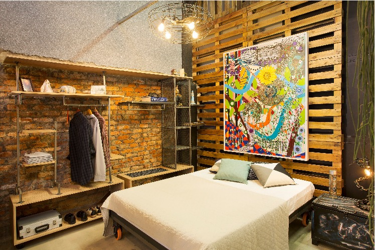 Mostra de decoração upcycling, na antiga fábrica Bhering. João Velloso e José Oliveira assinam o quarto de dormir: destaque para o painel de pallets atrás da cama e a luminária pendente com cúpula de um antigo ventilador