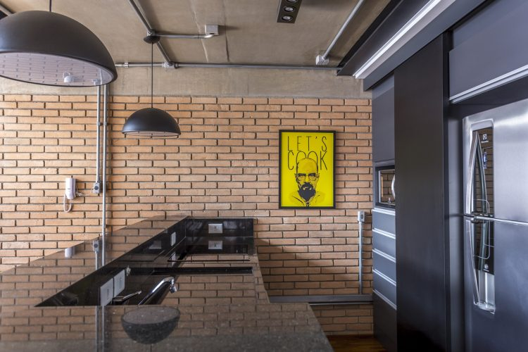 Cozinha com bancada preta no lojt masculino de Korman arquitetos