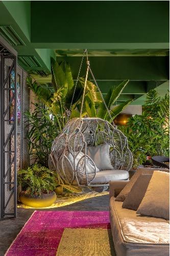 Cadeira de balanço com tramas de folhas.