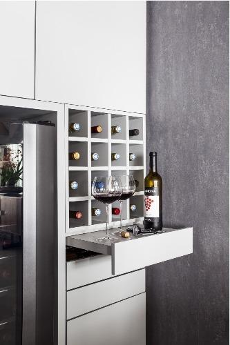 Urbanidade dá o tom para apartamento de família em SP. Adega climatizada e ao lado um gaveteiro com uma prateleira de apoio embutida.