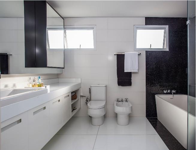 Urbanidade dá o tom para apartamento de família em SP. Banheiro em preto e branco com banheira branca.