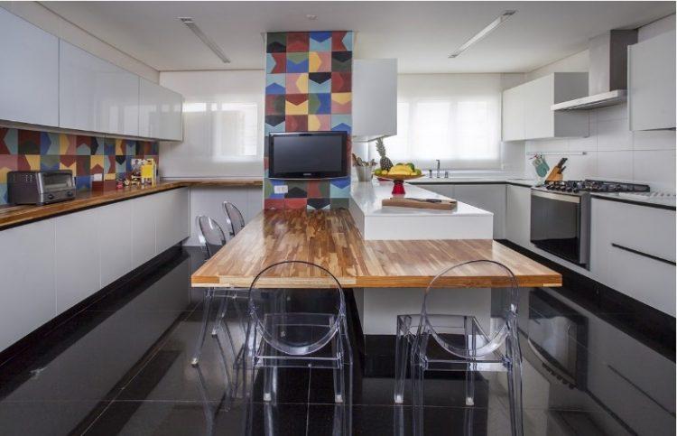 Urbanidade dá o tom para apartamento de família em SP. Cozinha com piso preto, armários brancos e com destaque do revestimento colorido em azulejo hidráulico.