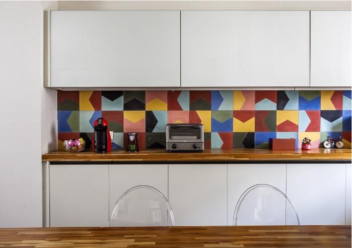 Urbanidade dá o tom para apartamento de família em SP. Destaque na cozinha, parede de funda da bancada de apoio revestida com azulejo hidráulico colorido.