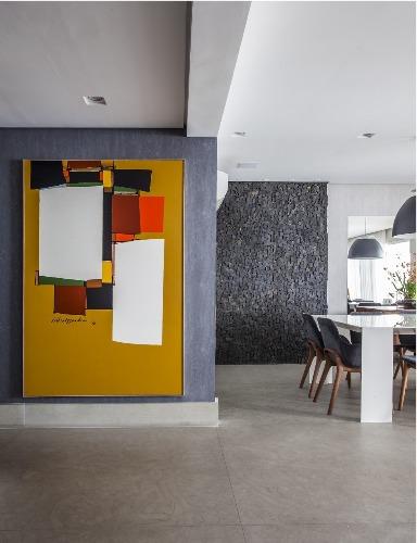 Urbanidade dá o tom para apartamento de família em SP. Parede cinza recebeu uma tela com fundo da cor mostarda com pintura moderna.