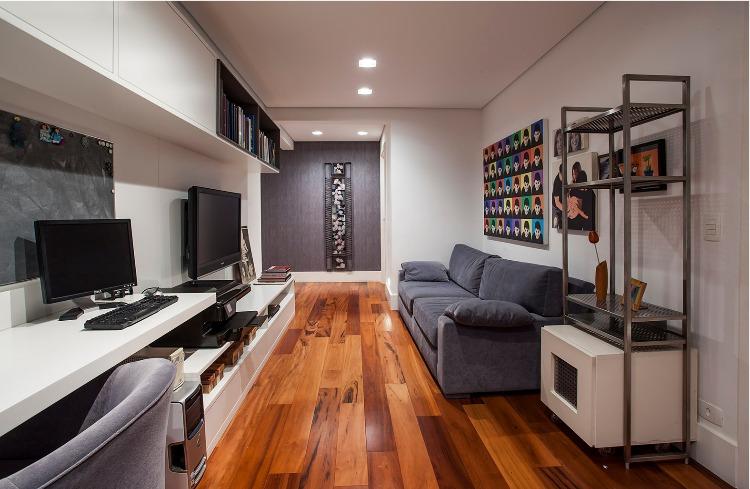 Urbanidade dá o tom para apartamento de família em SP. Espaço para a família curtir junto, com sofá cinza , computador e tv na parede.