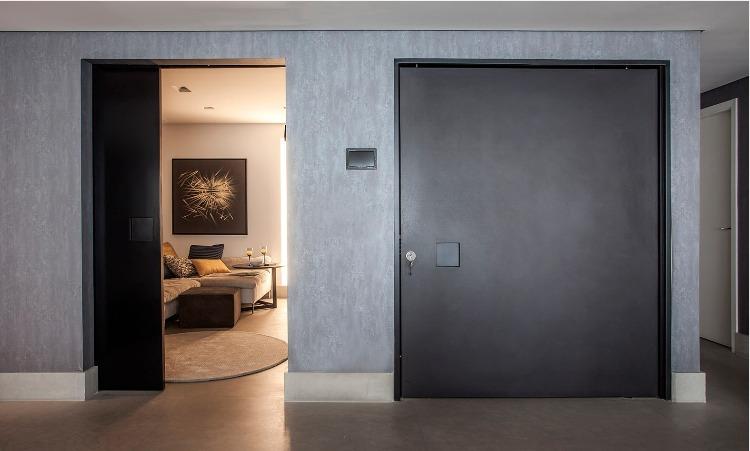 Urbanidade dá o tom para apartamento de família em SP. Portas de entrada grande na cor preta e ao lado uma porta de correr preta tb,