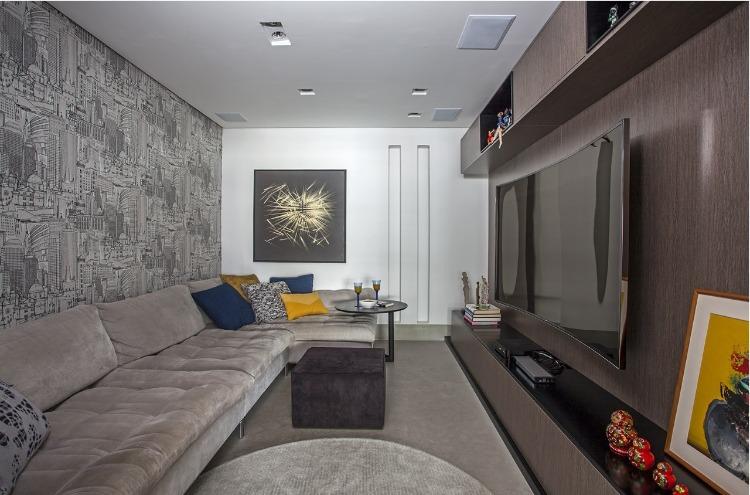 Urbanidade dá o tom para apartamento de família em SP. Sala de tv com sofá cinza a na parede um papel com o sky line da cidade de São Paulo.
