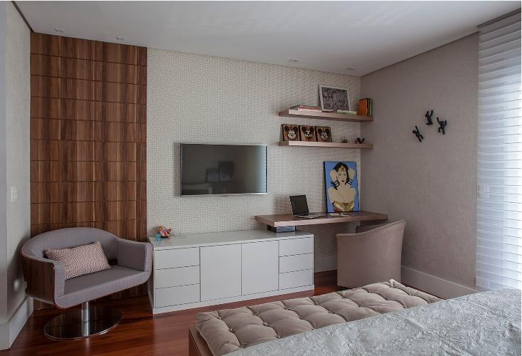 Urbanidade dá o tom para apartamento de família em SP. Bancada e tv na parede em frente a cama.