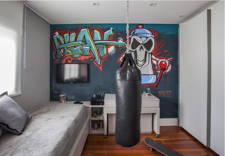 Urbanidade dá o tom para apartamento de família em SP. Quarto do filho decorado em tons de cinza, um grafitti na parede de fundo e um saco de boxe pendurado no meio do quarto,