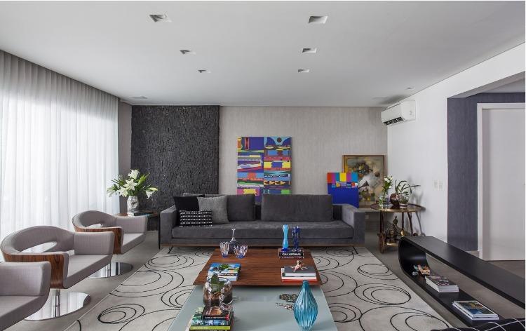 Urbanidade dá o tom para apartamento de família em SP. Living decorado em tons de cinza e uma tela colorida na parede.