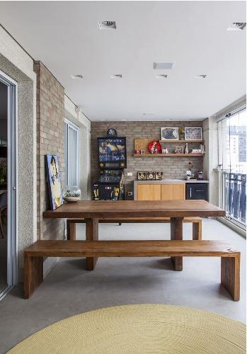 Urbanidade dá o tom para apartamento de família em SP. Varanda com fliperama e bancada.