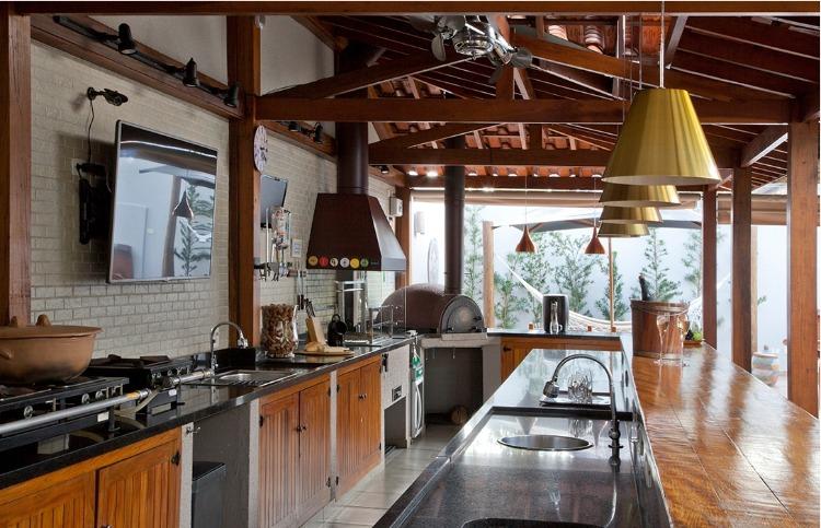 Edicula com uma grande cozinha, equipada com churrasqueira e forno de pizza.