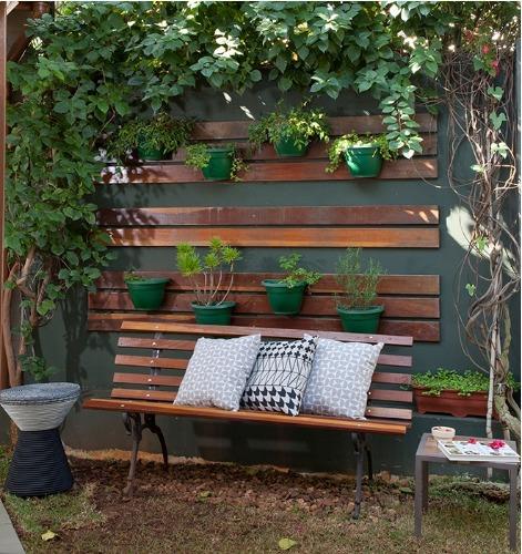 muro com horta vertical e um banquinho com almofadas.