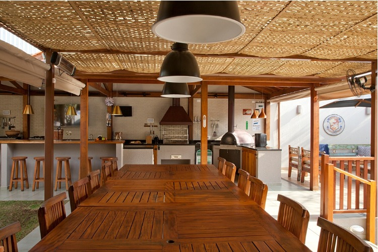 Edicula com mesa grande em madeira e teto revestido em palha.