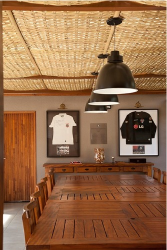Edicula com uma grande mesa em madeira, luminárias pendentes preta e teto revestido com palha.