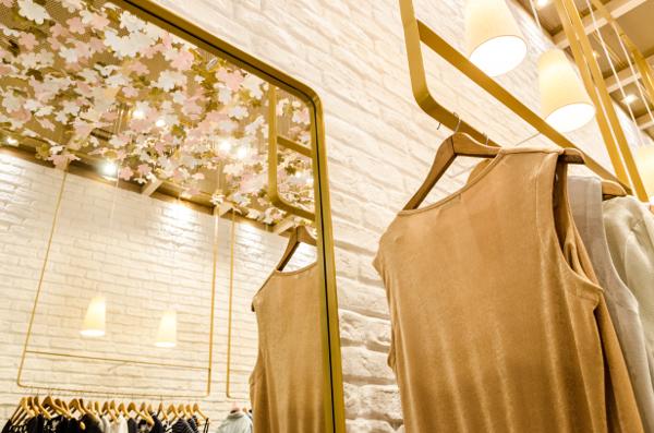 Penduradas no teto em módulos aramados, cerca de 2.500 pequenas flores confeccionadas pela artesã Rita Aranha foram pintadas individualmente nas cores dourado, rosa nude e branco, garantindo a personalidade e a identidade visual da marca.