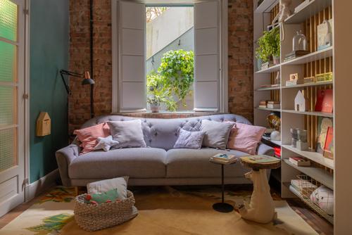 Sala de leitura, com sofá branco e parede de tijolinho original da casa, para mostra de decoração aonde as crianças são protagonistas.
