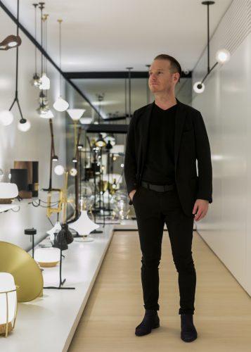 O designer Jader Almeida em meio à sua vasta coleção de luminárias