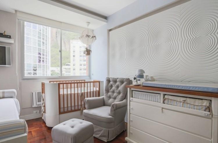 """Decoração de quarto de bebê. A paleta de cores do espaço éemtonsclaros, com paredesemcinzaenuances de branco, begeeazulemalguns detalhes do ambiente.""""O cinzaeo bege são cores que trazem tranquilidadeesobriedade."""