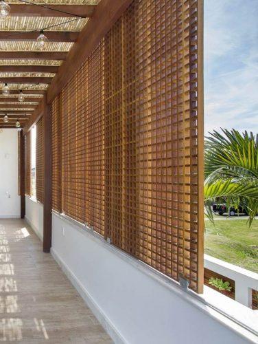 Painéis de treliça deslizantes fixados na fachada e paisagismo assinada por Carmem Mouro