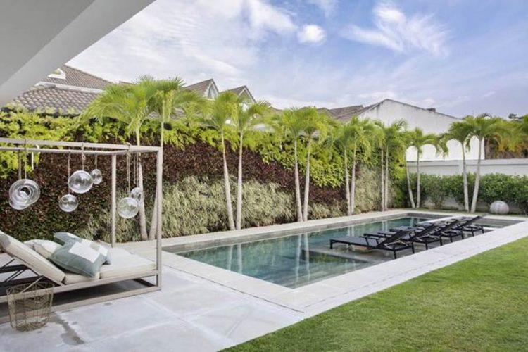 Piscina e gramado e paisagismo assinado por Carmen Mouro