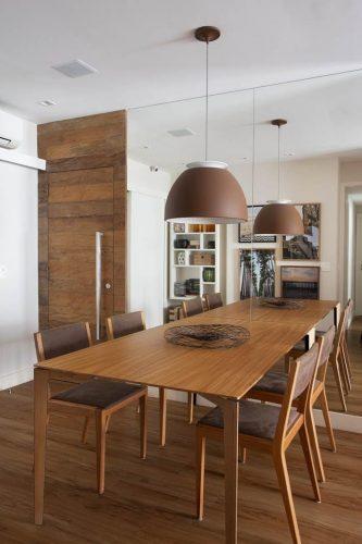 sala de jantar com mesa e porta de madeira no apto assinado por Bezamat Arquitetura