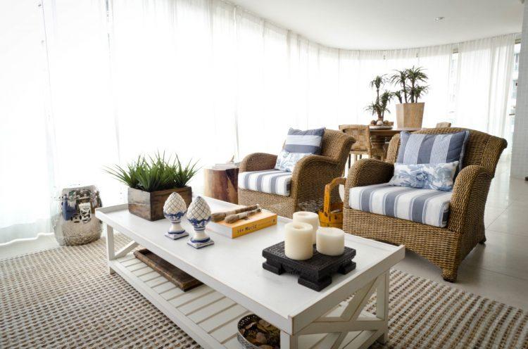 Varanda decorada em azul e branco , com móveis em fibra natural.