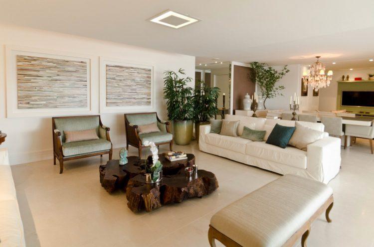 Living com decoração clássica, com tons claros e mesa de centro em tora de madeira.