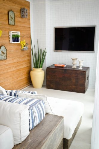 Varanda com televisão na parede e chaise lougue branca.