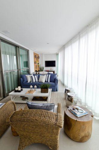 Varanda decorada com azul, branco e móveis em fibras naturais.