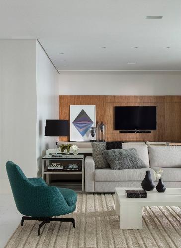 sala com painel de madeira e poltrona verde na sala de jacira pinheiro