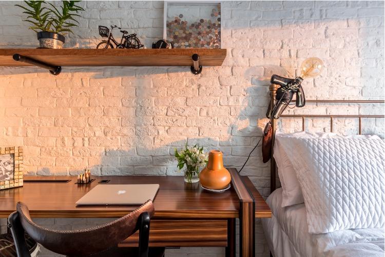 Cobertura em São Paulo com 540m² e cheia de boas ideias. Quarto com parede de tijolinho branco e prateleiras em madeira de demolição.