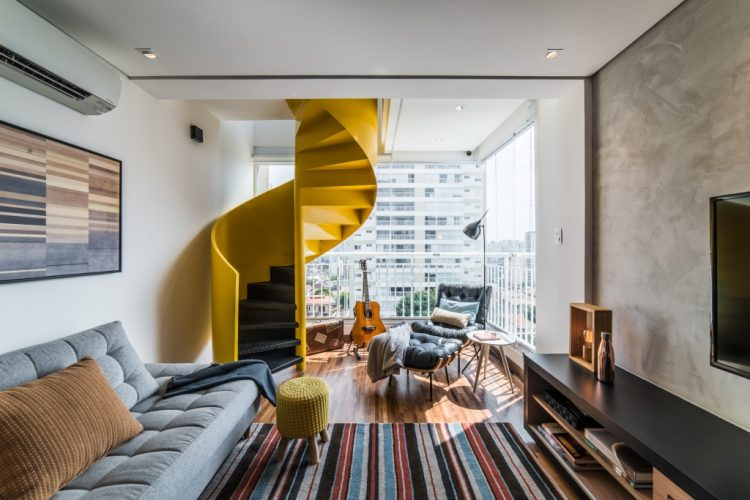 Sala com varanda e escada amarela no duplex assinado por Pietro Terilizzi