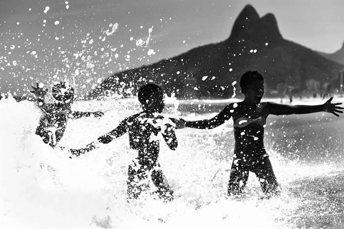 crianças na praia em frente ao morro dois irmãos feita por ari kaye