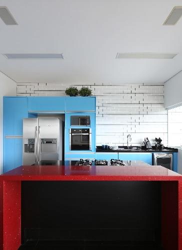 cozinha com armarios azuis e mesa vermelha no projeto da triarq arquitetura