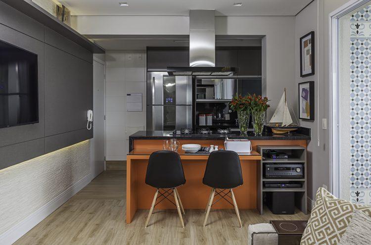 Cozinha americana com bancada laranja no projeto de Cristiane Schiavoni