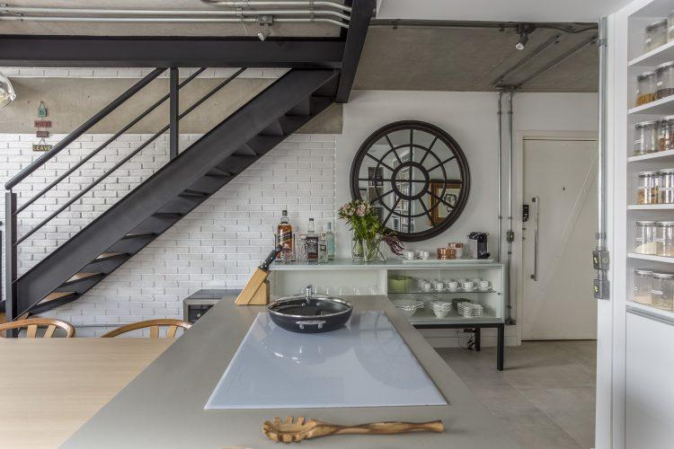 parede de tijolinhos brancos e escada de ferro assinada por Korman Arquitetos
