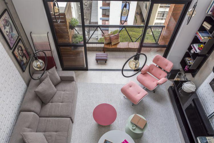vista area da sala assinada por Korman Arquitetos e poltrona Charles Eames em rosa