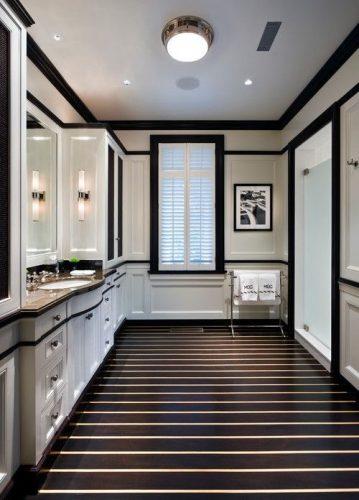 Rodapés pretos acrescenta personalidade ao Décor. Banheiro com piso preto listrado de branco, armarios e paredes brancas com detalhes em preto, como o rodapé e guarnição da janela e porta.