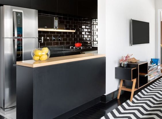 Rodapés pretos acrescenta personalidade ao Décor. Cozinha aberta para a sala que tem tapete na estampa chevron em preto e branco com o rodapé preto.