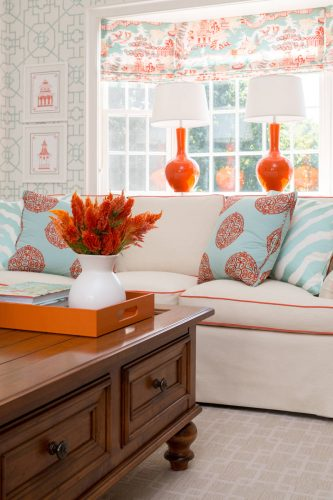 sofa branco e adornos com detalhes em coral