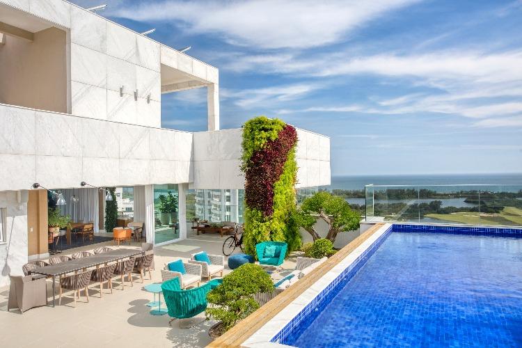 Piscina com parede verde e paisagismo assinado por Carmen Mouro