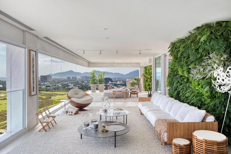 parede verde atras do sofá com paisagismo de Carmen Mouro