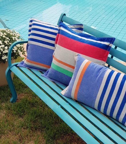 Toalhas de praia europeias viram almofadas exclusivas que são a cara do verão. Almofadas listradas de azul e vermelho.
