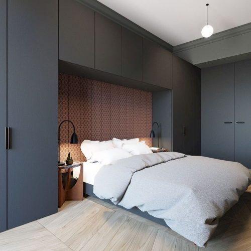 Armário com cama embutida. Porta azul marinho e funo da cama com tecido estampado em vermelho.