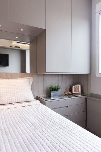 Armário com cama embutida e espelho em cima da cama.